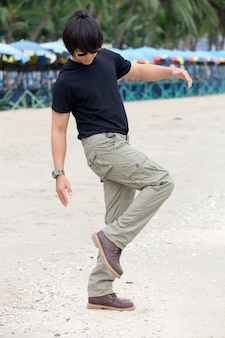 Guy wearing cargo pants and standing on the beach