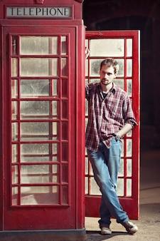 赤い電話ブースでチェックのシャツとジーンズを着ている男