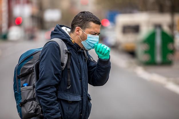 人混みの中で屋外のウイルスからの保護マスクを身に着けている男。コロナウイルスによる健康と安全の概念