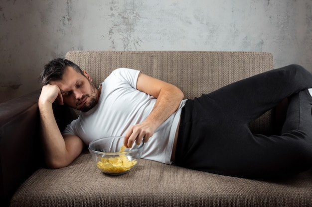 Guy wearing a white shirt is lying on the couch, eating chips and watching a sports channel.