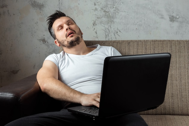 Guy wearing a white shirt sitting on the couch, fell asleep at work on a laptop.