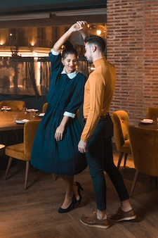 Guy whirling charming lady in restaurant