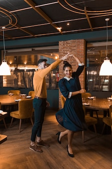 Guy whirling cheerful lady in restaurant