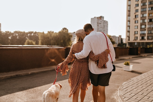Guy in white shirt and shorts is hugging his girlfriend in polka dot outfit. couple walking their white labrador.