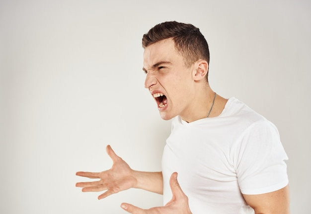 A guy in a white t-shirt emotions irritability light background inadequate state