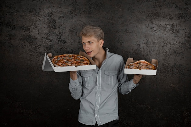 A guy in a white t-shirt holds boxes of pizza in his hands and greedily sniffs the smell on a black background. young man eating a slice of pizza with closed eyes, isolated on yellow background.
