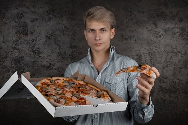 A guy in a white t-shirt holds a piece of pizza in his hands on a black background. young man eating a slice of pizza with closed eyes, isolated on yellow background.