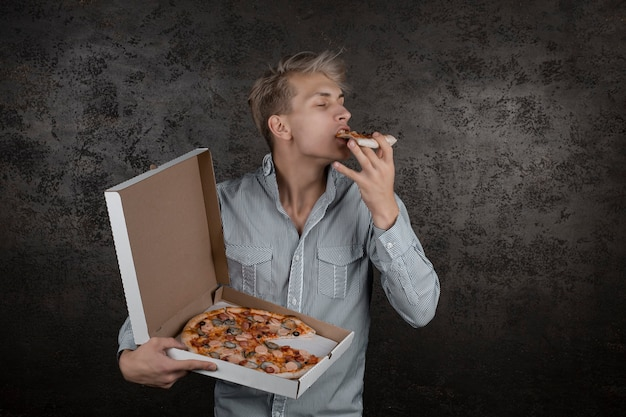 A guy in a white t-shirt holds a piece of pizza in his hands and eats fast food on a black background. young man eating a slice of pizza with closed eyes, isolated on yellow background.