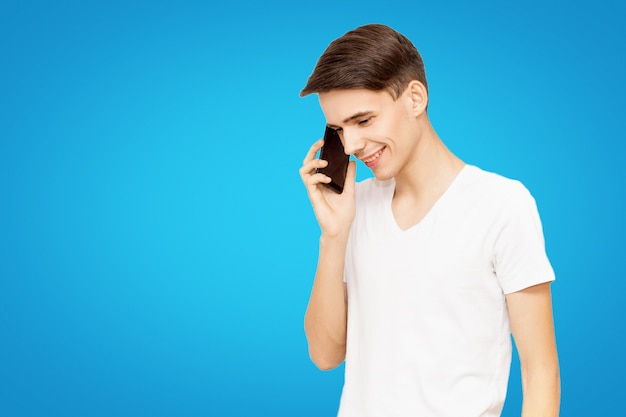 A guy in a white t-shirt talking on the phone on a blue isolated background, talkative young man, joyful man in life