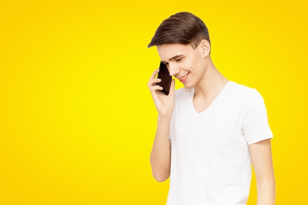 The guy in the white t-shirt talking on the phone on a yellow isolated background, talkative young man, joyful man in life