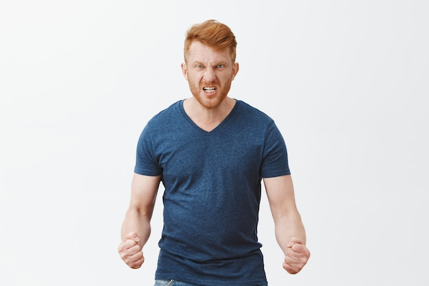 男は怒りがどのように見えるかを示します。怒りの表情、しわくちゃの鼻、眉をひそめ、危険なほどに拳を食いしばって、灰色の壁に憎しみを感じている怒りと怒りの危険な赤毛の男の肖像画