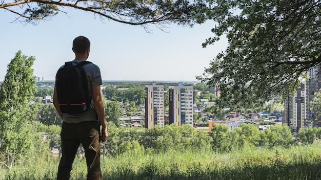 バックパックを背負った男が坂の上に立って街を眺めている。