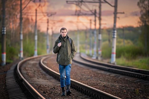 배낭을 든 남자가 여행을하고, 철로를 따라 간다