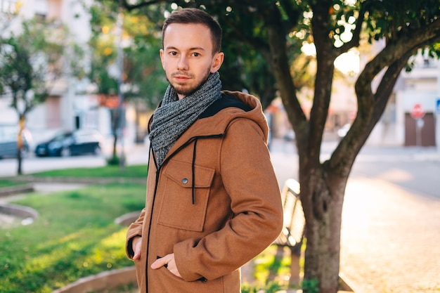 スタイリッシュなジャケットを着たあごひげを生やした男がカメラを見てください。街の通り。