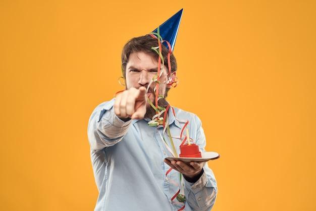 黄色の背景の休日のキャンドルクロップドビューでプレートにケーキを持つ男