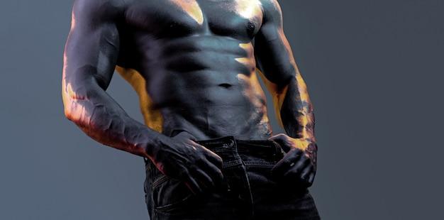 벌거 벗은 몸통 근육질의 남자가 네온 검정 파란색 배경 위에 아령으로 운동