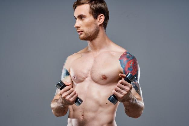 裸の胴体を持った男が腕の筋肉をポンプでくみ上げたダンベルフィットネスボディービルスポーツ