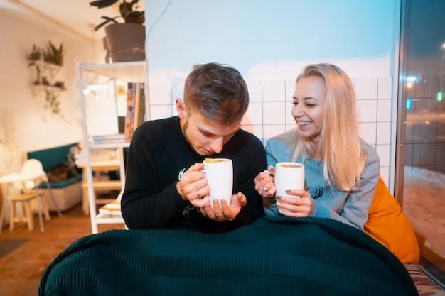 Парень с молодой женщиной пьют горячий кофе и чай