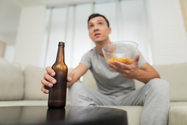 Guy with beer and chips watching tv.
