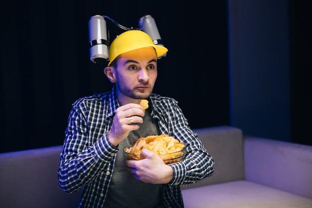 머리에 맥주 헬멧을 쓴 남자가 소파에 앉아 칩을 먹고 tv를 본다.
