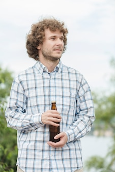 Guy with beer in nature