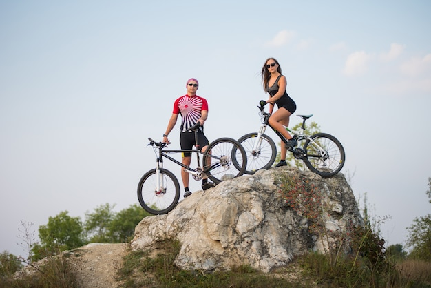 Guy with bicycle with pretty fitness girl on a mountain bike standing on a rock
