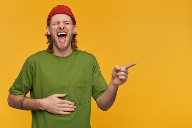 Парень со светлыми волосами и бородой. в зеленой футболке и красной шапке. прикосновение к животу и сильный смех с закрытыми глазами. указывая пальцем вправо на место для копирования, изолированное над желтой стеной