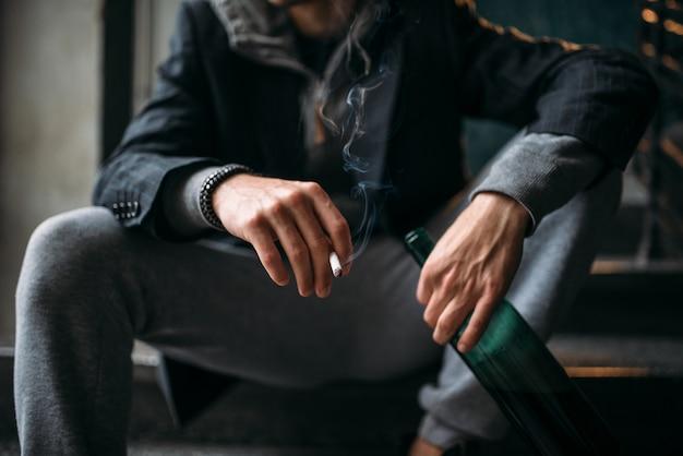 Парень с бутылкой сидит на лестнице и курит