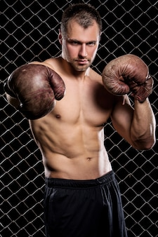 Guy with a boxing gloves showing muscles on fence