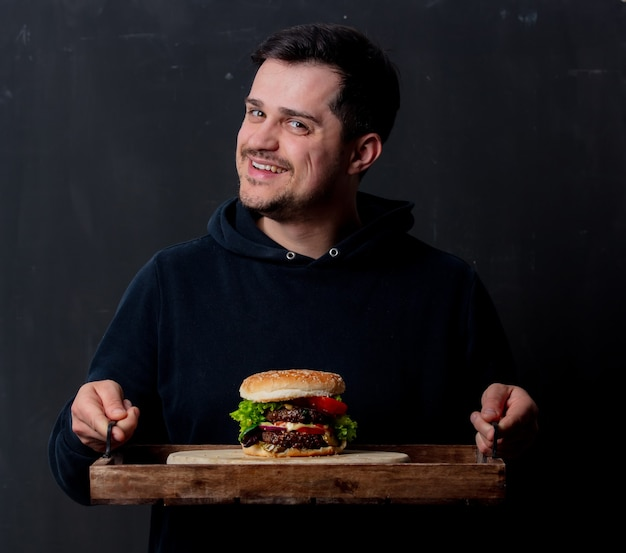 Guy with classic american burger on tray