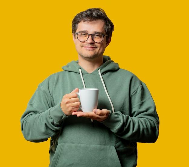 노란색에 커피와 녹색 까마귀의 컵을 가진 남자
