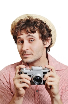 Guy with curly hair in a hat with a vintage camera takes pictures