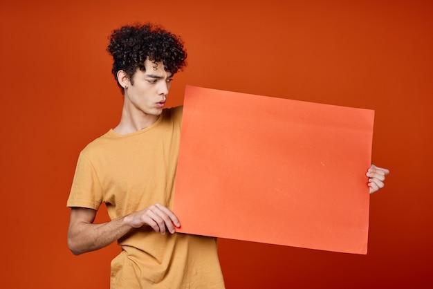 赤いコピースペースのポスターを保持している巻き毛の男