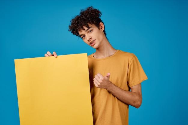Парень с вьющимися волосами держит в руках желтый плакат с рекламой. фото высокого качества
