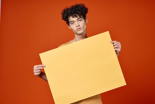 赤い背景を宣伝する手に巻き毛の島を持つ男