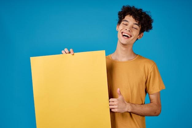 彼の手のスタジオの青い背景に黄色のアスターの巻き毛を持つ男
