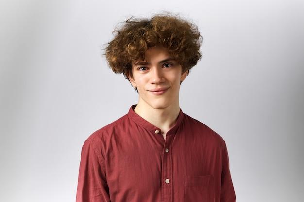 Ragazzo con i capelli ricci che sorride di buon umore, rallegrandosi di notizie positive.