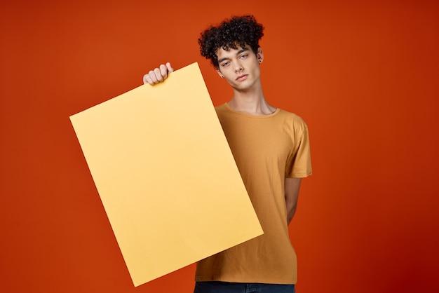 Парень с вьющимися волосами рекламный макет студии красный фон
