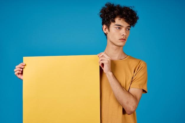 Парень с вьющимися волосами, желтые плакаты в руках, копия пространства синий фон студия