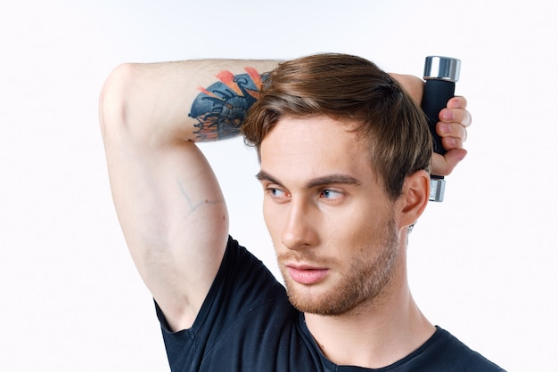 ダンベルを持つ男は彼の頭の後ろに彼の手を保持し、明るい背景の黒いtシャツスポーツフィットネス