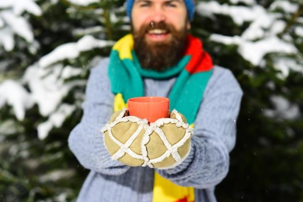 背景に雪で覆われたモミの木を持った男、焦点がぼけています。男は笑顔でニットスカーフと手袋を着用しています。カップまたはマグカップを保持している暖かい手袋の手。温かい飲み物のコンセプト。
