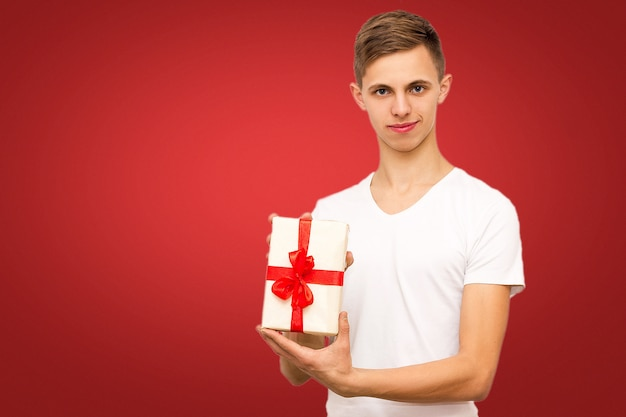 Guy with a gift on a red background, portrait of a guy on a red background with a place under the inscription