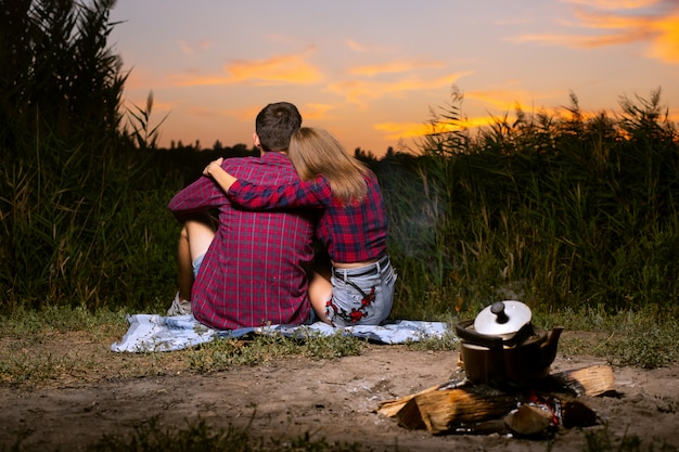 Guy with a girl in red checkered shirts are sitting in an embrace on the river bank