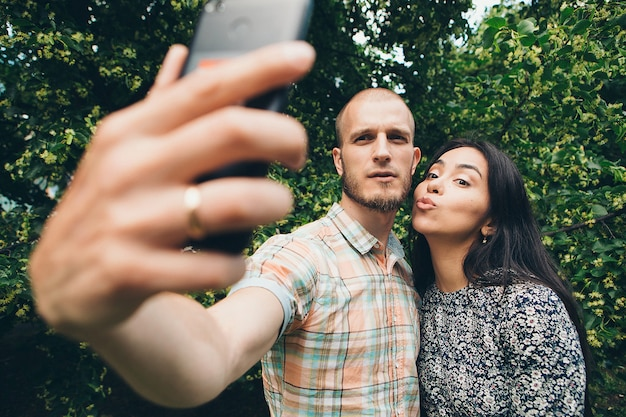 A guy with a girl taking selfies on a green foliage.