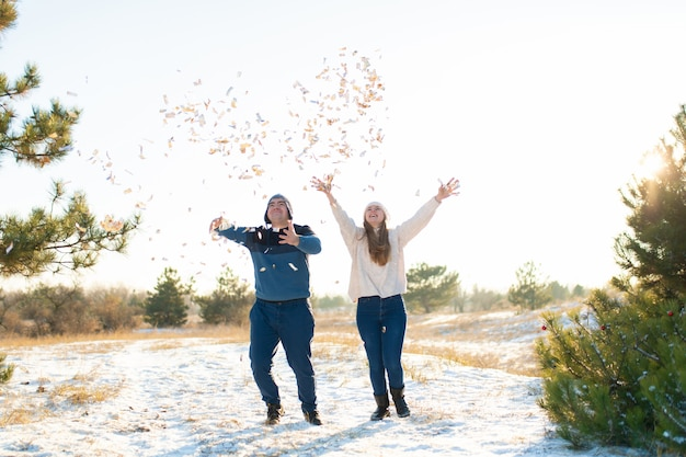 Guy with girl throw confetti in the winter forest