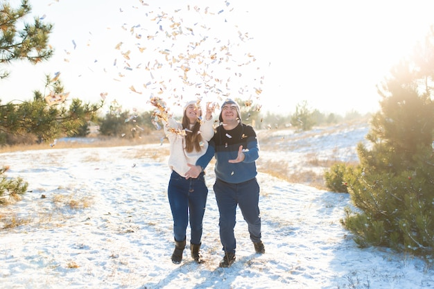The guy with the girl throw confetti in the winter forest