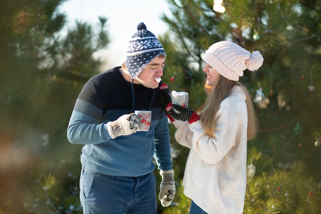 The guy with the girl walk and kiss in the winter forest with a mug of hot drink