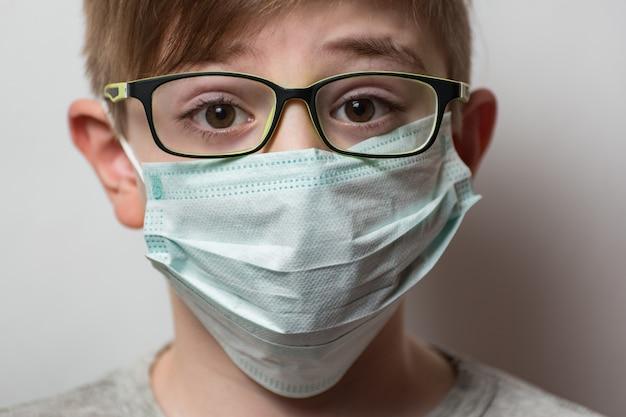 メガネと医療マスクを持つ男。インフルエンザウイルスの保護。子供の肖像画をクローズアップ。