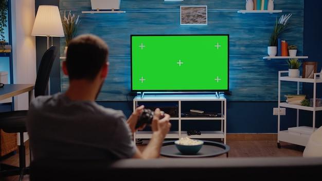 リビングルームに緑色の画面のモダンなテレビを持つ男