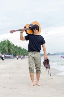 Guy with guitar standing on the beach,  cargo pants